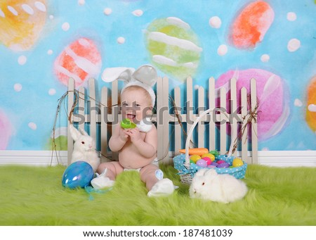 happy baby boy with easter headband sitting in easter scene - stock photo