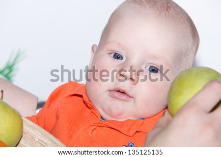 happy baby boy with green apples