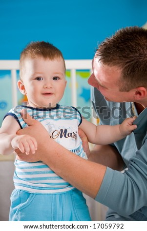 Happy baby boy ( 1 year old ) and father playing together at children's room, smiling.