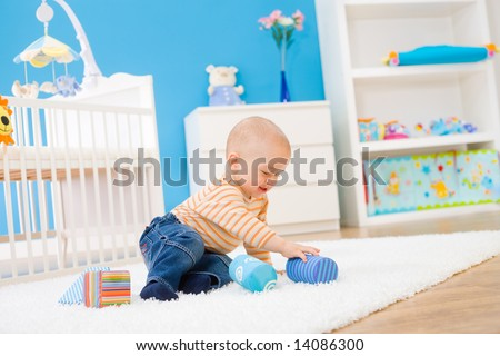 Happy baby boy (1 year old) sitting on floor at children's room and playing with toy blocks. Toys are officially property released. - stock photo