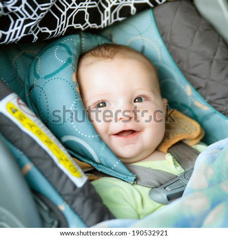 Happy baby buckled into rear-facing car seat - stock photo