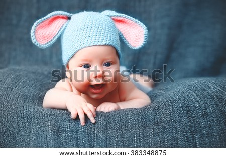 happy baby child in costume a rabbit bunny   on a grey background - stock photo