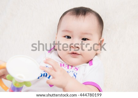 Happy baby child relaxing in bed. Nursery for young children.