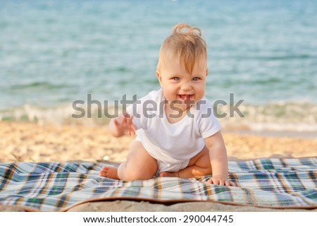Happy baby crawling on the beach. Summer vacation.  - stock photo