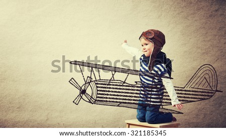 Happy baby dreams of becoming a pilot aviator and plays with planes on background wall of house - stock photo