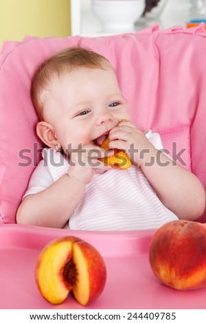 Happy baby eating fruit - stock photo