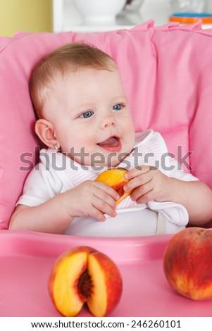 Happy baby eating fruit - stock photo
