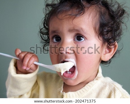 Happy baby eating porridge with spoon - stock photo