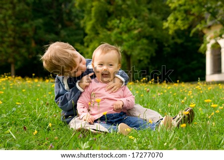 Happy baby girl and young brother sat in together in field.