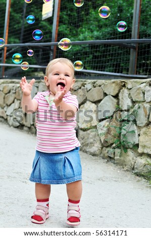 happy baby girl catching soap bubbles in the park
