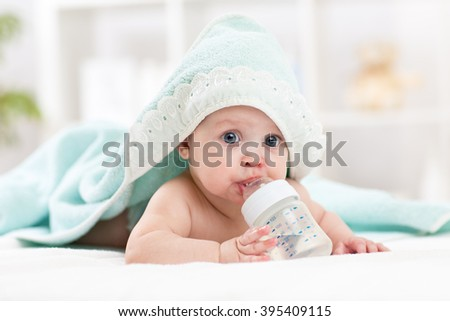 Happy baby girl drinks water from bottle wrapped towel after bath - stock photo