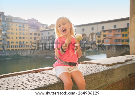 Happy baby girl eating ice cream near ponte vecchio in florence, italy - stock photo