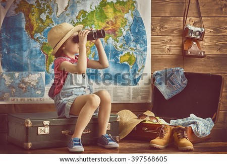 happy baby girl getting ready for the journey. Girl packs her bags and playing with binoculars.