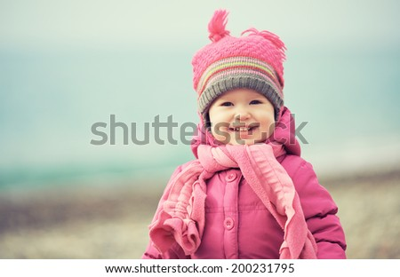 Happy baby girl in a pink hat and scarf laughs - stock photo