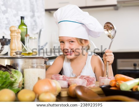 Happy baby girl in cook hat cooking soup - stock photo