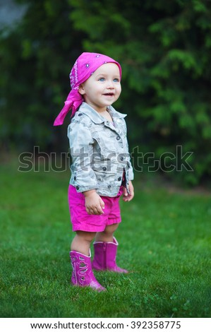 Happy baby girl in red boots walking on the meadow. - stock photo