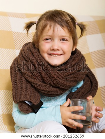 Happy baby girl in warm scarf with glass - stock photo