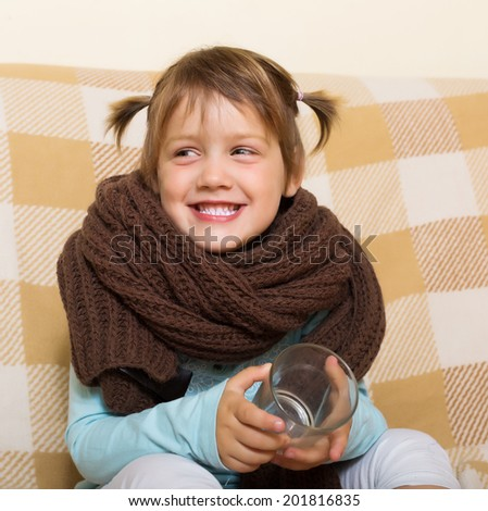 Happy baby girl in warm scarf with glass on couch - stock photo
