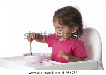 Happy Baby girl is eating by herself - stock photo