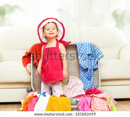 happy baby girl is going on a trip, pack a suitcase - stock photo