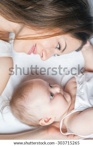 Happy baby girl lying near her mother on a white bed. Girls looking at each other. Mother care is most important in baby life - stock photo