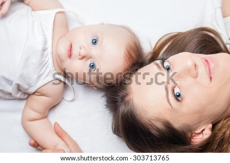 Happy baby girl lying near her mother on a white bed. Newborn looking at the camera. Mothercare is most important in baby life - stock photo