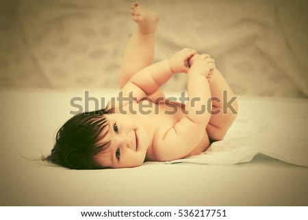 Happy baby girl lying on blanket at home