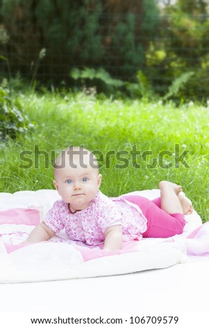 happy baby girl lying on lawn, discovering nature and learning how to crawl.