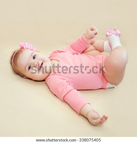 Happy baby girl playing with her feet on a beige background. - stock photo