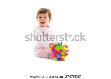 Happy baby girl sitting on floor playing with toy smiling, isolated on white background. - stock photo