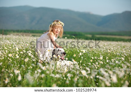Happy baby girl stroking her dog in camomile field