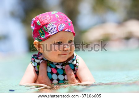 Happy baby girl swimming in a pool - stock photo
