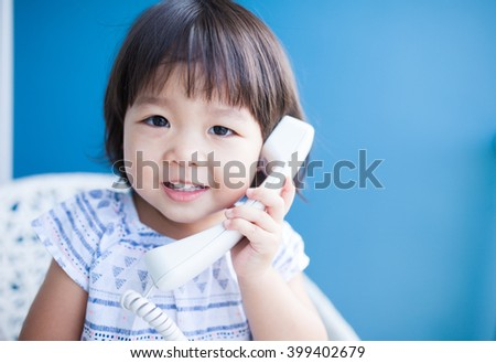 Happy baby girl talking on phone on blue background - stock photo