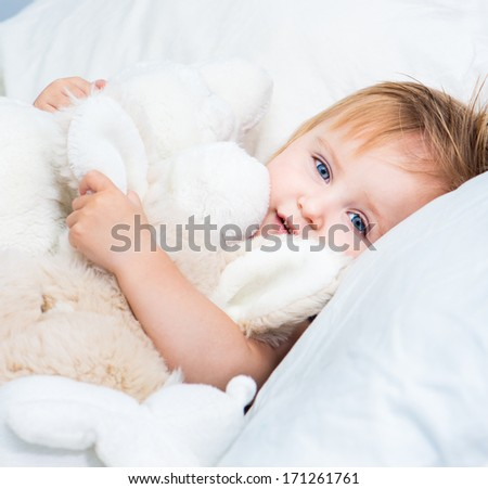happy baby girl with a toys lying in white bed