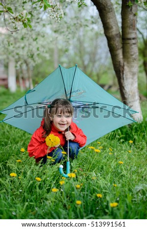 happy baby girl with an umbrella in the park