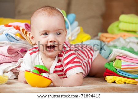 Happy baby girl with heap of baby's things - stock photo