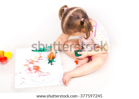 Happy baby girl with her hands in paint drawing isolated on white. Art concept, early education