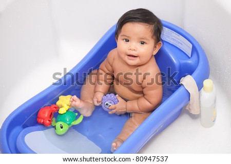 Happy baby in bathtub with water toys - stock photo