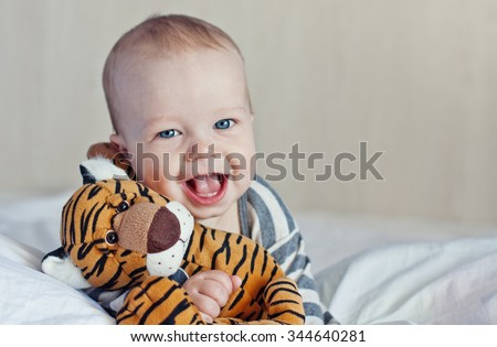 Happy baby in bed with a favorite toy - stock photo