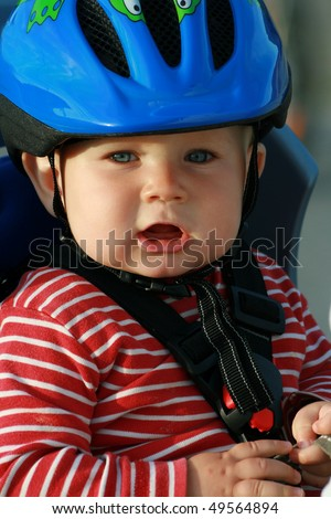 Happy baby in bicycle chair. 10 months old baby boy in helmet.