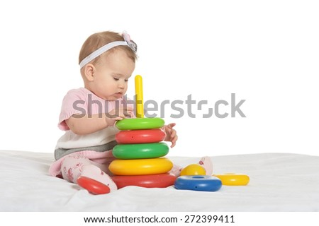 Happy baby in pink clothes playing with toys on a white background - stock photo
