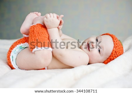 happy baby is laying and catching own legs - stock photo