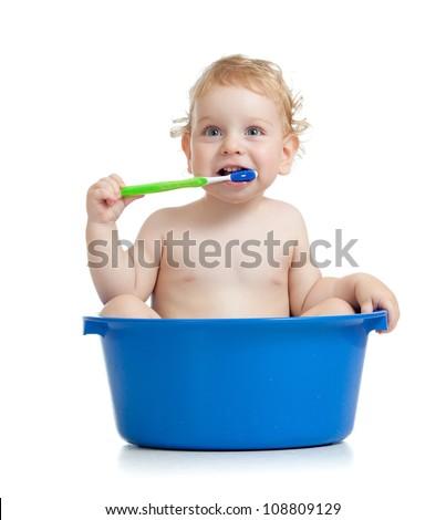 Happy baby kid brushing teeth sitting in basin - stock photo