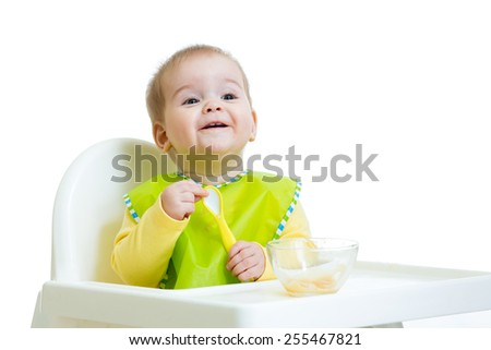 happy baby kid waiting for food with spoon at table - stock photo