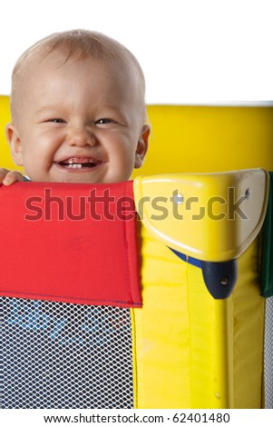 Happy Baby Laughing in Colorful Travelling Cot - stock photo