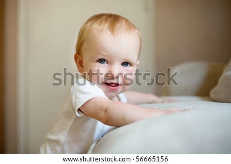 Happy baby learning to stand - stock photo