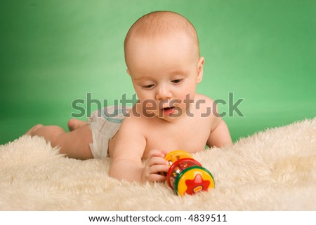 Happy baby lie on carpet and playing - stock photo