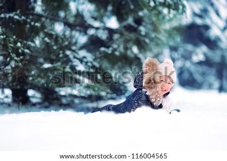 happy baby lying in the snow - stock photo