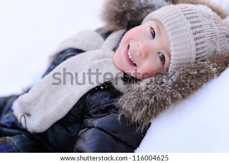 happy baby lying in the snow. Winter and cold.