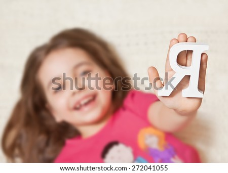 """Happy baby lying on the floor holding before the English letter """"I"""". The concept of personality. - stock photo"""